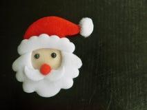 圣诞老人的面孔有胡子和红色盖帽的,毛毡,黑背景 库存图片