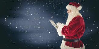 圣诞老人的综合图象使用一台片剂个人计算机 库存照片