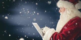 圣诞老人的综合图象使用一台片剂个人计算机 库存图片