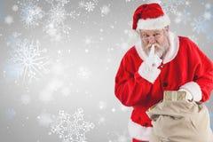 圣诞老人的综合图象有手指的在嘴唇和举行礼物 免版税库存照片