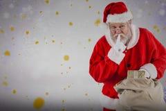 圣诞老人的综合图象有手指的在嘴唇和举行礼物 免版税库存图片