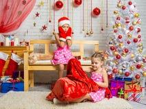 圣诞老人盖帽和手套的女孩看见袋子攀登另一个女孩 免版税库存照片
