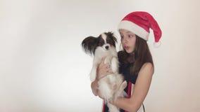 圣诞老人盖帽和狗大陆玩具西班牙猎狗的Papillon唬弄美丽的青少年的女孩快乐亲吻和  股票录像