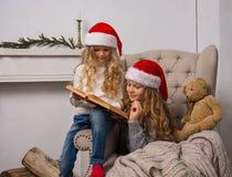 圣诞老人盖帽的两个小女孩读一本书 库存照片
