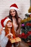 圣诞老人盖帽的两个微笑的朋友有好时光在基督附近 免版税库存图片