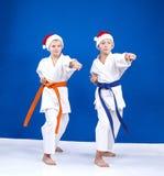 圣诞老人盖帽的两个男孩击中了在空手道机架的拳打胳膊  免版税库存照片