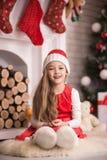 圣诞老人盖帽的可爱的女孩坐地板,演播室射击,定调子在葡萄酒样式 库存照片