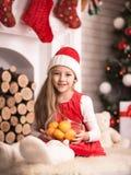 圣诞老人盖帽的可爱的女孩用在手中蜜桔,演播室射击,定调子在葡萄酒样式 免版税图库摄影
