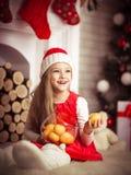 圣诞老人盖帽的可爱的女孩用在手中蜜桔,演播室射击 免版税图库摄影