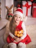 圣诞老人盖帽的可爱的女孩用在手中蜜桔,演播室射击 免版税库存照片