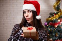 圣诞老人盖帽的年轻美丽的妇女有在圣诞节的一个礼物盒的 库存照片
