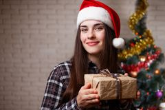 圣诞老人盖帽的年轻美丽的妇女有在圣诞节的一个礼物盒的 免版税库存图片