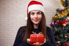 圣诞老人盖帽的年轻美丽的愉快的妇女有在chri的一个礼物盒的 免版税库存图片