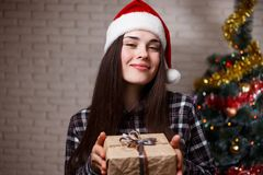 圣诞老人盖帽的年轻美丽的愉快的妇女有在chri的一个礼物盒的 图库摄影