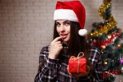 圣诞老人盖帽的年轻逗人喜爱的妇女得到了在圣诞树ba的一个礼物 免版税库存照片
