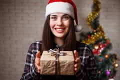 圣诞老人盖帽的年轻逗人喜爱的妇女是愉快得到在克里斯的一个礼物 免版税库存照片