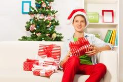 圣诞老人盖帽的男孩坐有礼物的沙发 免版税库存照片