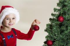 圣诞老人盖帽的装饰圣诞树的愉快的男孩画象  免版税库存照片