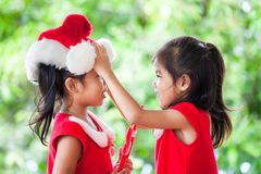 圣诞老人礼服的两个亚裔儿童女孩互相帮助穿戴 库存图片