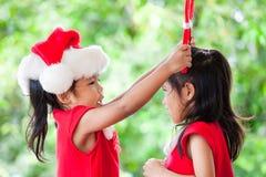 圣诞老人礼服的两个亚裔儿童女孩互相帮助穿戴 库存照片