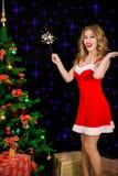 圣诞老人礼服的俏丽的妇女有在黑背景的闪烁发光物的 图库摄影