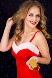 圣诞老人礼服的愉快的妇女有在黑背景的礼物的 图库摄影