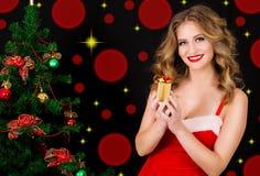 圣诞老人礼服的愉快的妇女有在黑背景的礼物的 免版税库存图片