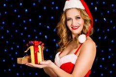 圣诞老人礼服的愉快的妇女有在黑背景的礼物的 库存图片