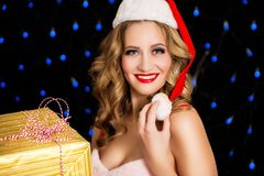 圣诞老人礼服的愉快的妇女有在黑背景的礼物的 库存照片