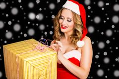 圣诞老人礼服的愉快的妇女有在黑背景的礼物的 免版税库存照片
