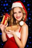 圣诞老人礼服的愉快的妇女有在黑背景的礼物的 免版税图库摄影