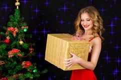 圣诞老人礼服的美丽的妇女有在黑背景的礼物的 免版税库存照片