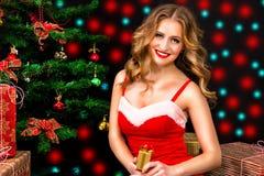 圣诞老人礼服的美丽的妇女有在黑背景的礼物的 免版税图库摄影