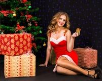 圣诞老人礼服的美丽的妇女有在黑背景的礼物的 库存照片