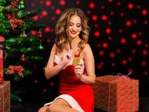 圣诞老人礼服的美丽的妇女有在黑背景的礼物的 库存图片
