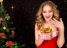 圣诞老人礼服的美丽的妇女有在黑背景的礼物的 免版税库存图片