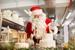 圣诞老人糕点业者一个蛋糕在圣诞节的Da厨房里 免版税库存照片