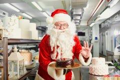 圣诞老人糖果商在基督的厨房里烹调一个蛋糕 免版税图库摄影