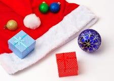 圣诞老人红色和白色帽子、玩具泡影和圣诞节礼物 免版税库存照片