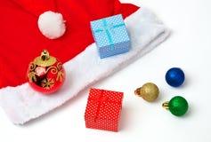 圣诞老人红色和白色帽子、玩具泡影和圣诞节礼物 免版税图库摄影
