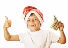 圣诞老人红色帽子的小逗人喜爱的男孩隔绝与现金美国美元赞许愉快的孩子假日庆祝 库存照片