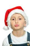 圣诞老人红色帽子的微笑的男孩 图库摄影