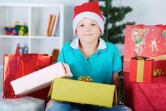 圣诞老人红色帽子的滑稽的男孩有很多礼物盒的 免版税库存图片