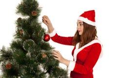 圣诞老人红色礼服的美丽的少妇dreesed绿色杉树 免版税库存图片