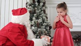 圣诞老人给当前一个惊奇的小女孩和拥抱她 免版税库存照片