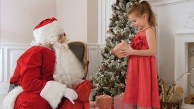 圣诞老人给当前一个惊奇的小女孩 库存照片