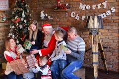圣诞老人给新年礼物大家庭在装饰的屋子里 免版税库存照片