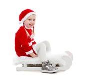 圣诞老人衣服的快乐的小女孩坐雪橇 免版税库存图片