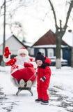 圣诞老人衣服的爸爸和他的乘坐爬犁的小儿子在冬天雪下,在村庄街道 免版税库存图片