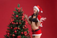 圣诞老人衣裳的妇女在圣诞树附近的 免版税库存照片
